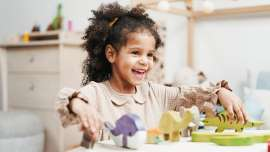 selective focus photo of laughing young girl playing with wooden toys on white table