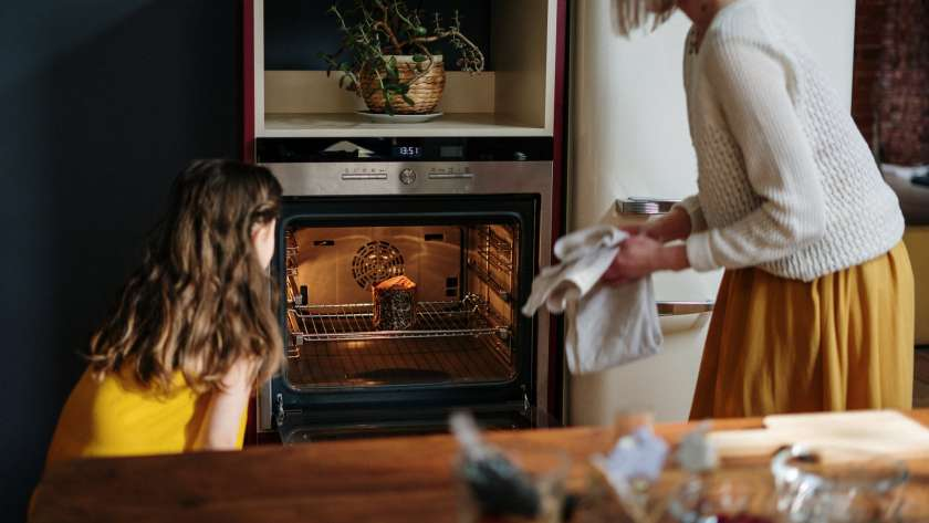 mom and daughter baking a cake